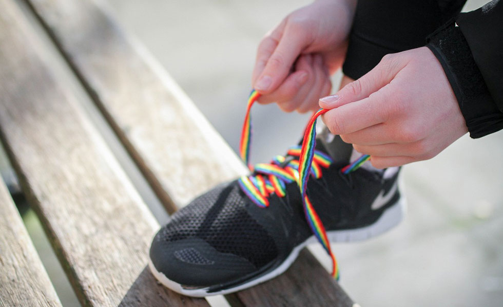 Photo: a person tying up their trainers with rainbow laces