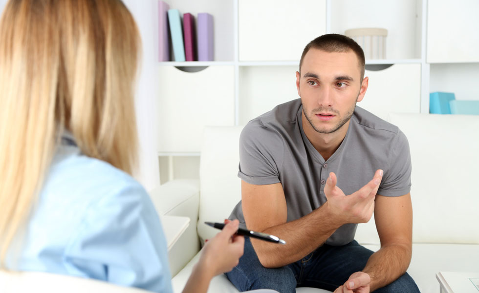 Photo: a young man talking to a counsellor