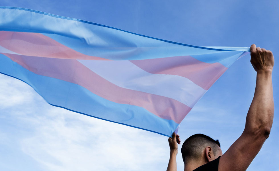 Photo: a transgender man with a pride flag blowing behind him