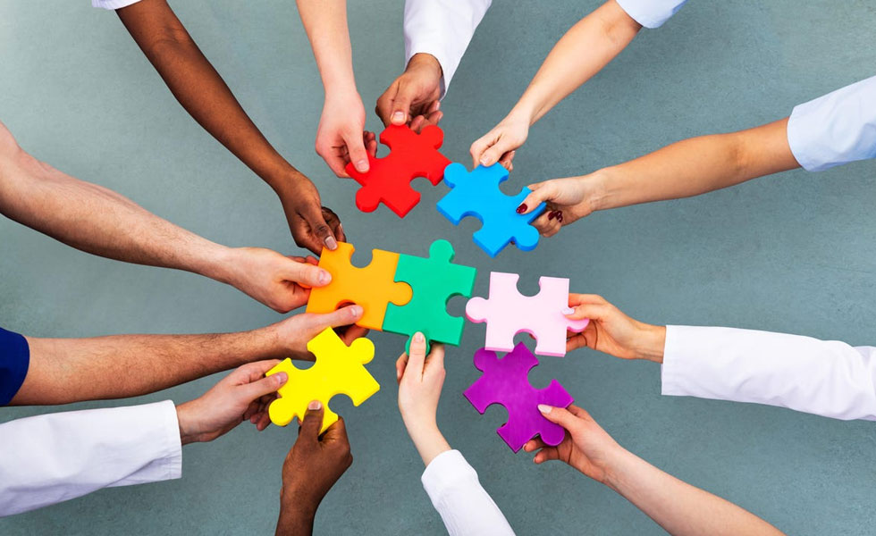 Photo: diverse hands holding mulitcoloured jigsaw pieces